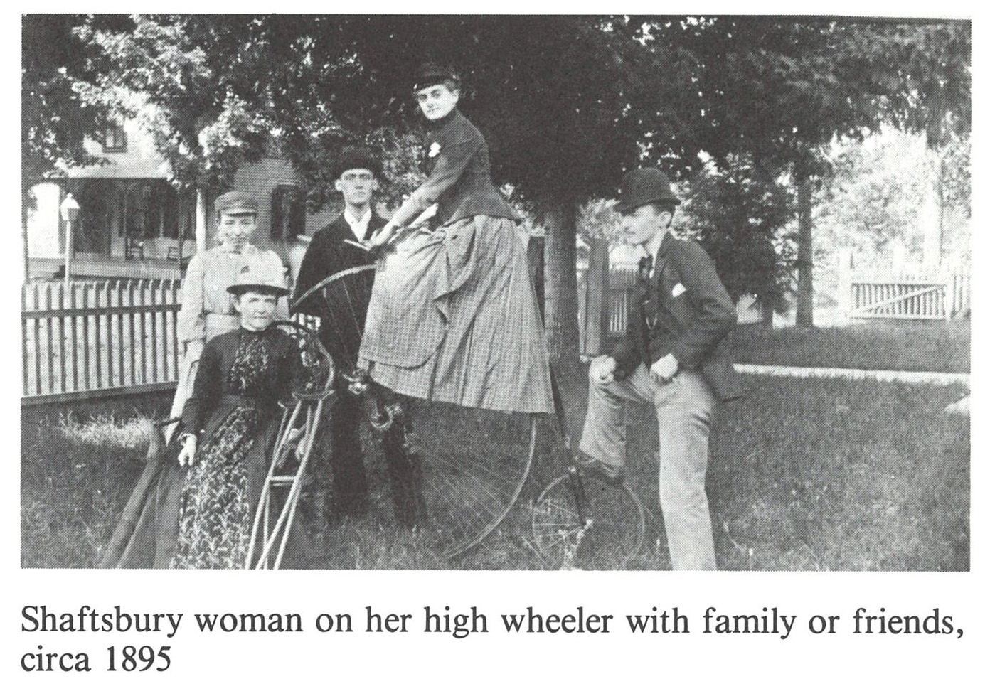 Historic photograph of a group of people, including a women riding a high-wheeler bicycle.