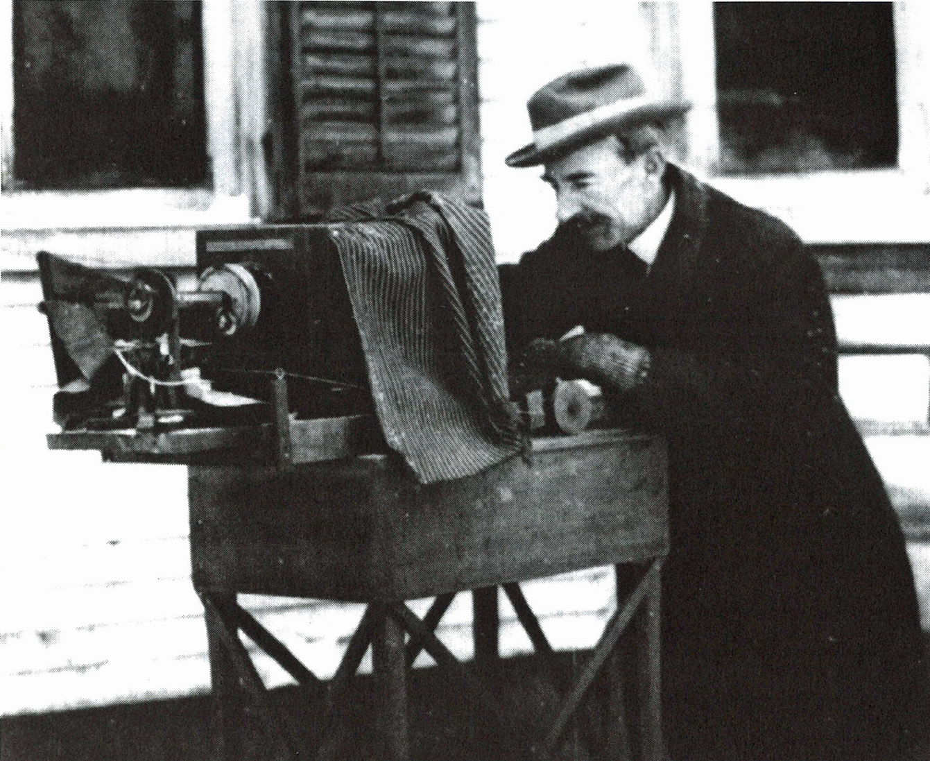 Historic photograph of man outside with a large camera.