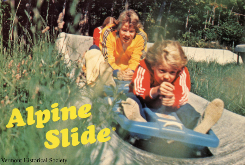 A historic photo showing two children on an alpine slide.